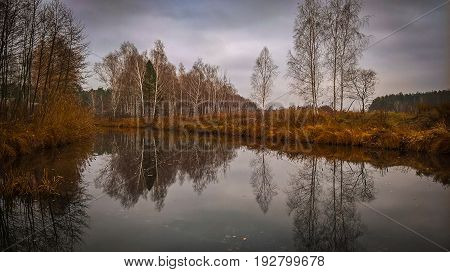 A lake reflecting a gloomy autumn sky.
