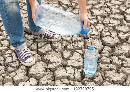 the human pours in an empty plastic bottle drinking water against the background of the dry soil. Concept of Global drought, warming, summer, thirst .
