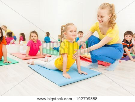 Portrait of cheerful female gymnastic instructor helping little girl doing back stretching on yoga mat in gym
