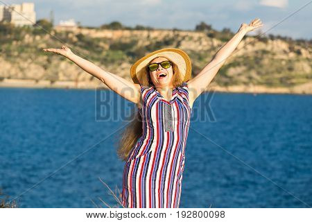 Portrait of young woman on the beach near the sea with hands up wearing dress and hat.