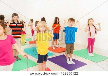 Group of 5-6 years old kids standing in two lines and jumping with skipping rope in gym