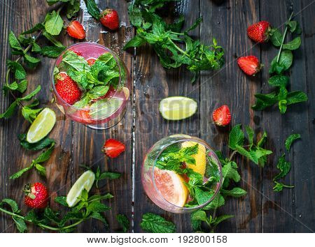 Strawberry cocktails with lime and ice cubes on rustic background. Top view