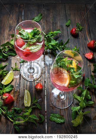 Strawberry cocktails with lime and ice cubes on rustic background.