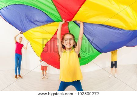 Happy six years old girl waving rainbow parachute during sports festival at school gym
