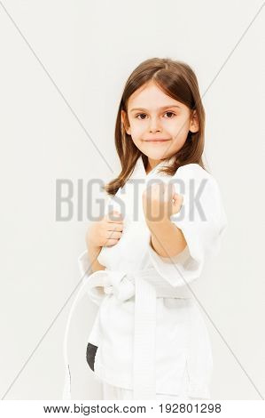 Portrait of six years old girl in white kimono training karate against background with copy-space