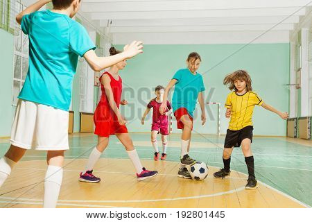 Portrait of 11-12 years old boys and girls playing football in school sports hall