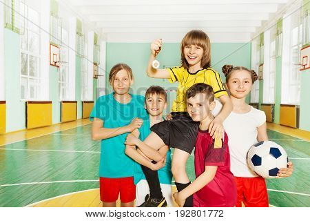 Portrait of preteen boys and girls, soccer team, celebrating victory, lifting up captain with trophy