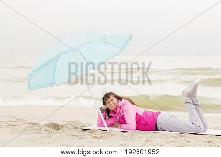 Photo of beautiful girl in a coat lying on a sandy beach with blue beach umbrella