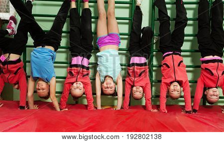 Preteen boys and girls making handstand position standing in line next to the wall-mounted gym ladder
