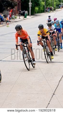 STILLWATER, MINNESOTA/USA - JUNE 18, 2017: Pro women cyclists race downhill at the 2017 North Star Grand Prix Stillwater Criterium. Emma White (second racer in yellow) is the overall race winner.