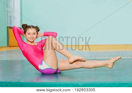 Portrait of smiling 12 years old girl doing bicycle crunches on the mat in school sports hall
