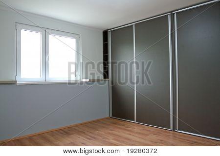 New empty bedroom with window and wardrobe