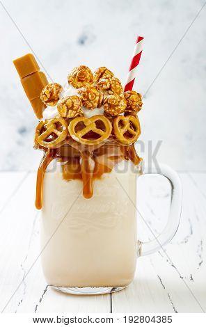 Salted caramel indulgent extreme milkshakes with brezel waffles popcorn and whipped cream. Crazy freakshake food trend.