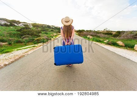 Beautiful young lady travelling with a suitcase, rear view