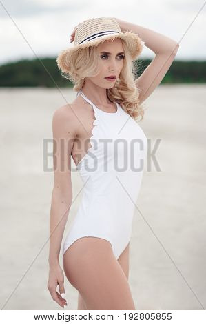 Beautiful blond woman in a white bathing suit and hat posing standing on beach