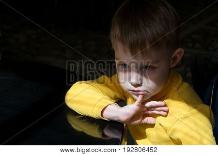 Little boy sitting at the table in a pensive state. The boy backs her fingers to her lower lip. He looks forward and thinks sad sad or disappointed. He has the intelligent look.