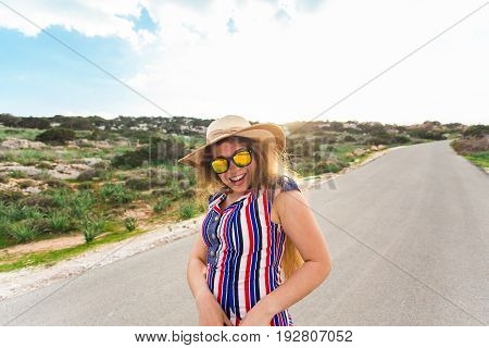 summer holidays, vacation, travel and people concept - smiling laughing young woman wearing sunglasses and hat on the road.