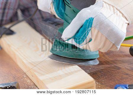 Man sanding a wood with orbital sander in a workshop