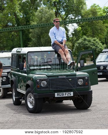 BEAULIEU HAMPSHIRE UNITED KINGDOM - JUNE 25 2017 Land Rover day with many varieties of Land Rovers including this green Land Rover Defender with a man sitting on the roof waiting in queue of Land Rovers.