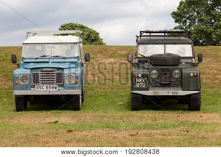 BEAULIEU HAMPSHIRE UNITED KINGDOM - JUNE 25 2017 Land Rover day with many varieties of Land Rovers including these Land Rover Series 2 and Series 3 parked side by side on the grass on a cloudy day.