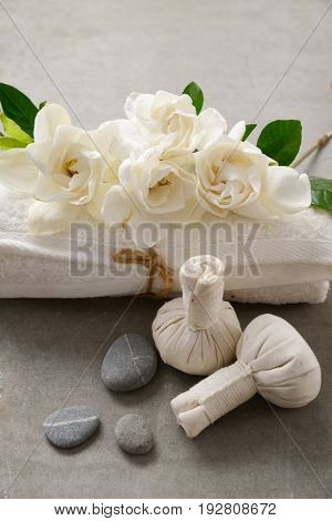 Spa setting with Gardenia flowers and ball, salt in bowl, in basket on gray background