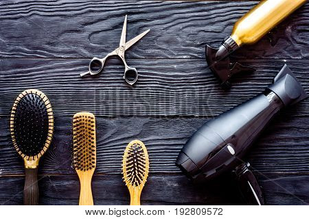 Comb brushes, hairdryer and hairspray on grey wooden background top view.