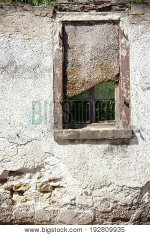 A nailed window in a ruin wall with crumbling plaster.
