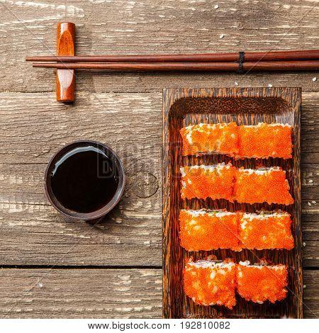 Photo rolls on rectangular plate, black chopsticks, soy sauce on wooden table