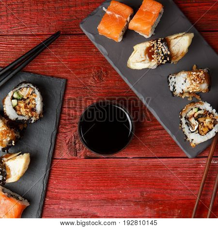 Rolls served on black boards at red wooden table