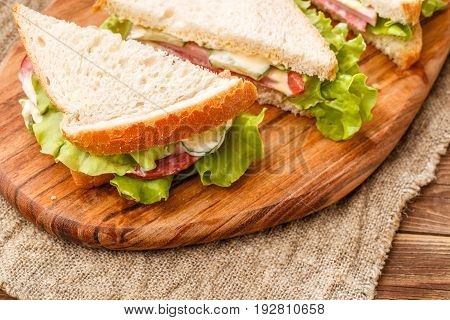 Photo of fresh sandwiches on wooden board at canvas fabric