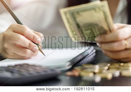 Close up hand female with pencil writing on the book and hand hold US dollar. Calculation at home