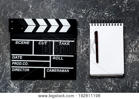 Work table of producer. Movie clapperboard and notebook on grey stone background top view.