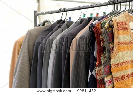 Selection Of Classic Men's Jackets And Blazers And Knitwear Hanging On A Rail