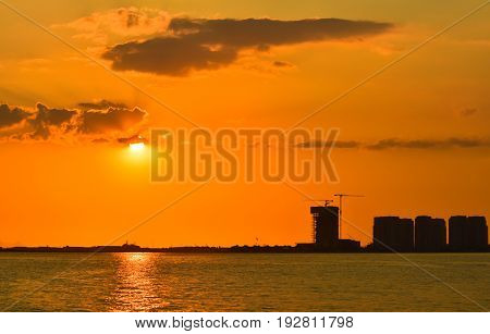 Silhouette of building under construction and the construction crane or power crane sunset time with cloudy sky.