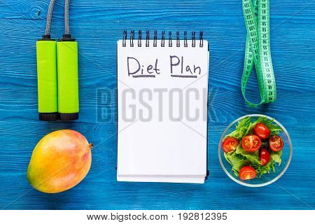 Tasty food for slimming. Notebook for diet plan, salad, fruits and measuring tape on blue table top view mock up.