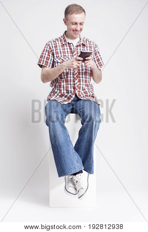 Youth Lifestyle Concepts and Ideas. Portrait of Positive Caucasian Man with Handheld Cellphone Chatting While Sitting on White Box.Vertical Image