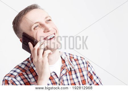 Youth Lifestyle Concepts and Ideas.Closeup Portrait of Smiling Happy Caucasian Man Speaking on Cellphone. Posing Against White Background. Horizontal Image