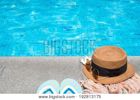 Concept of holiday tropical on summer Accessories blue slippers rainbow scarf straw hat coral and sunglasses on border of a swimming pool.