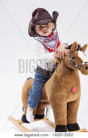 Children Consepts. Calm and Confident Little Caucasian Girl in Cowgirl Clothing On Symbolic Horse Against White Background.Vertical Image Composition
