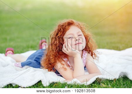 Portrait of cute funny happy smiling little red-haired Caucasian girl child in blue dress lying on green grass in park outside dreaming thinking lifestyle childhood concept