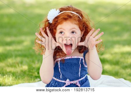 Portrait of cute adorable little red-haired Caucasian girl child in blue dress making funny silly faces showing tongue in park outside playing crying screaming having fun lifestyle childhood