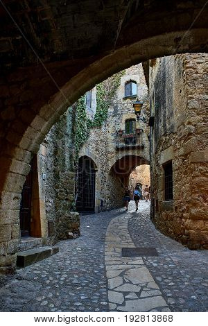 Pals Spain - June 22 2017. People walking in a doorgang of Carrer Major street in the medieval historic downtown of Pals. Bajo Ampurdan Girona Catalonia Spain.