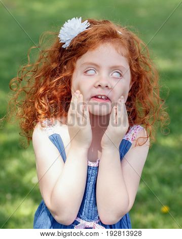 Portrait of cute adorable little red-haired Caucasian girl child in blue dress making funny scary silly faces in park outside child rolling eyes having fun lifestyle childhood concept