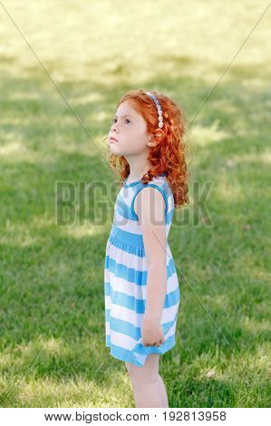 Portrait of cute adorable little red-haired Caucasian girl child in blue dress standing in field meadow park outside looking up in the air having fun happy lifestyle childhood concept