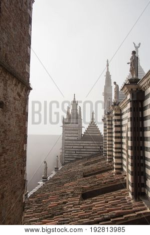 Italy Siena - December 26 2016: the view of the tiled roof arched windows and marble statues on Duomo di Siena on December 26 2016 in Siena Tuscany Italy.