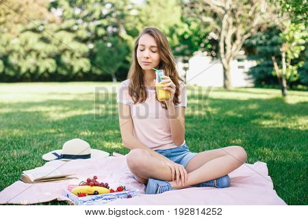 Portrait of young beautiful white Caucasian woman girl sitting on grass in park with closed eyes drinking fruit juice on summer day toned with retro filters film effect rural country lifestyle
