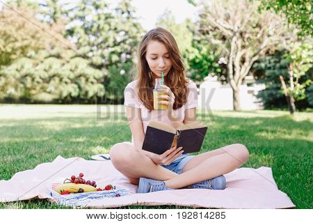 Portrait of young beautiful white Caucasian woman girl sitting on grass in park drinking fruit juice nd reading book on summer daytoned with retro filters film effect rural country lifestyle