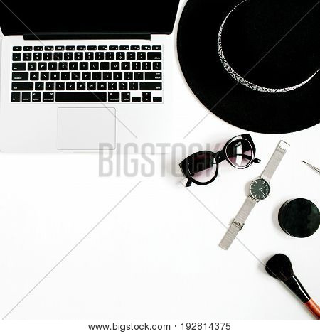 Fashion blogger office desk with laptop and black styled woman clothes and accessories collection on white background. Flat lay top view.