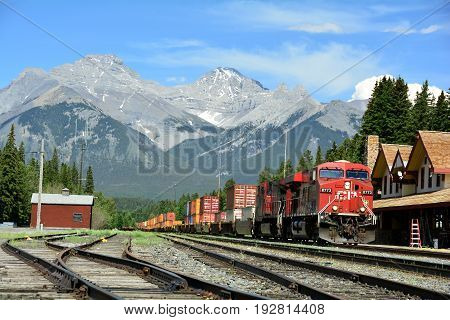 Banff National Park,Alberta Canada,June 28th 2011.A cargo train passes through Banff train depot on its way to the west coast leaving awesome mountain landscape in its wake.