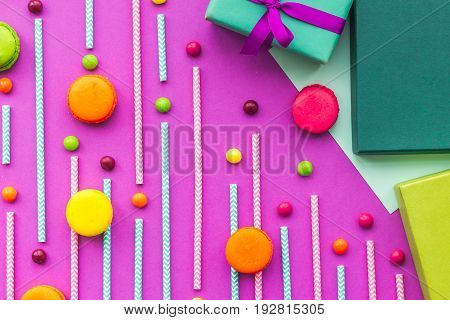 Birthday greeting cards, wrapped gifts and sweets on fuchsia background top view.